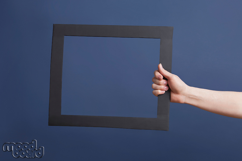 Hand holding frame over blue background