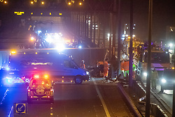 © Licensed to London News Pictures. 01/04/2020. Gerrards Cross, UK. An overturned HGV on the northbound carriageway of the M40 motorway between junction 1 and junction 2 alongside workers inspecting damage to the median barrier. The M40 motorway was closed in both directions due to a Road Traffic collision involving a heavy goods vehicle and at least to cars. Photo credit: Peter Manning/LNP