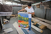 A Nepalese factory worker shows a small finished carpet handmade in the R.C rug factory in the Narayanthan area of Kathmandu, Nepal.  Larger finished rugs have been rolled up while other rugs are hanging to dry. These rugs are exported to Europe the U.S and Canada.