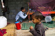 A nephew walks past as Ratna Baniya (28) ties the mosquito net to the bed while his youngest daughter Sapana Baniya (2 months) sleeps in a basket in their temporary home in Chautara, Sindhupalchowk, Nepal on 29 June 2015. The three girls lost their mother during the April 25th earthquake that completely levelled their house. Aastha was buried under the rubble together with her mother but Aastha survived. As their father Ratna Baniya (28) cannot care for the children on his own, SOS Childrens Villages has since been supporting the grandmother with financial and social support so that she can manage to raise the children comfortably and ensure that they will all be schooled. Photo by Suzanne Lee for SOS Children's Villages
