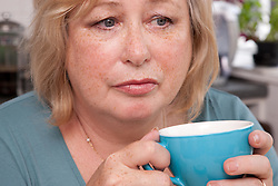 Thoughtful woman drinking tea