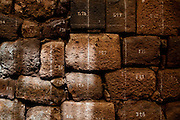 The bricks on a stone wall are numbered