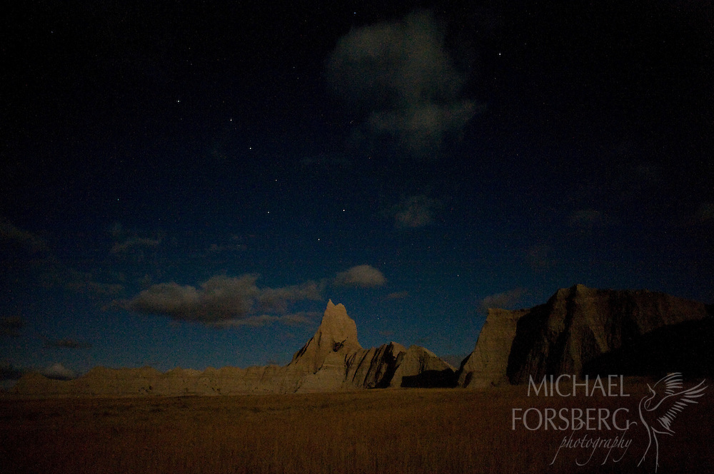 Northern Great Plains region:  Buffalo National Grassland - Sage Creek Wilderness Area boundary, Conata Basin, South Dakota..Full moon light in and out of cloud shadows casts a glow on a badlands formation