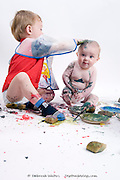 Little boy enjoying creative playtime painting his baby sister in a whirl of messy paint splatter, isolated on white