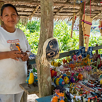 A local Peruvian woman holds a handicraft made of chambira palm fiber at her stand in Casual off of the Marañon River. Pacaya Samiria National Reserve, Upper Amazon, Peru.