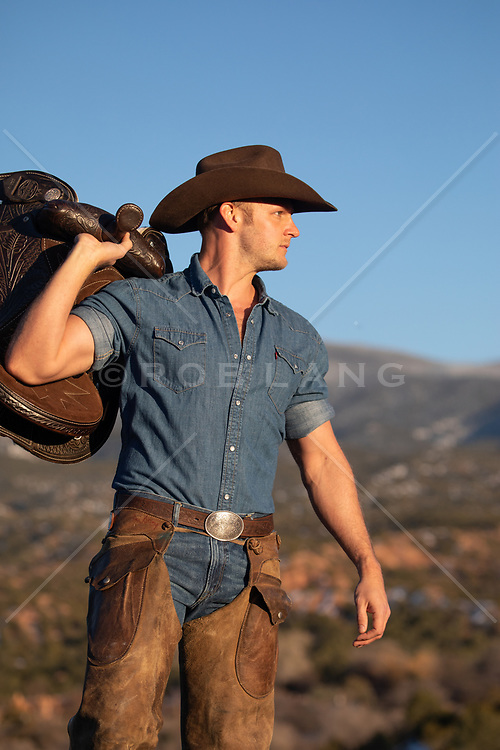hot rugged cowboy in chaps holding a saddle on a mountain top