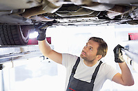 Male repair worker examining car in workshop