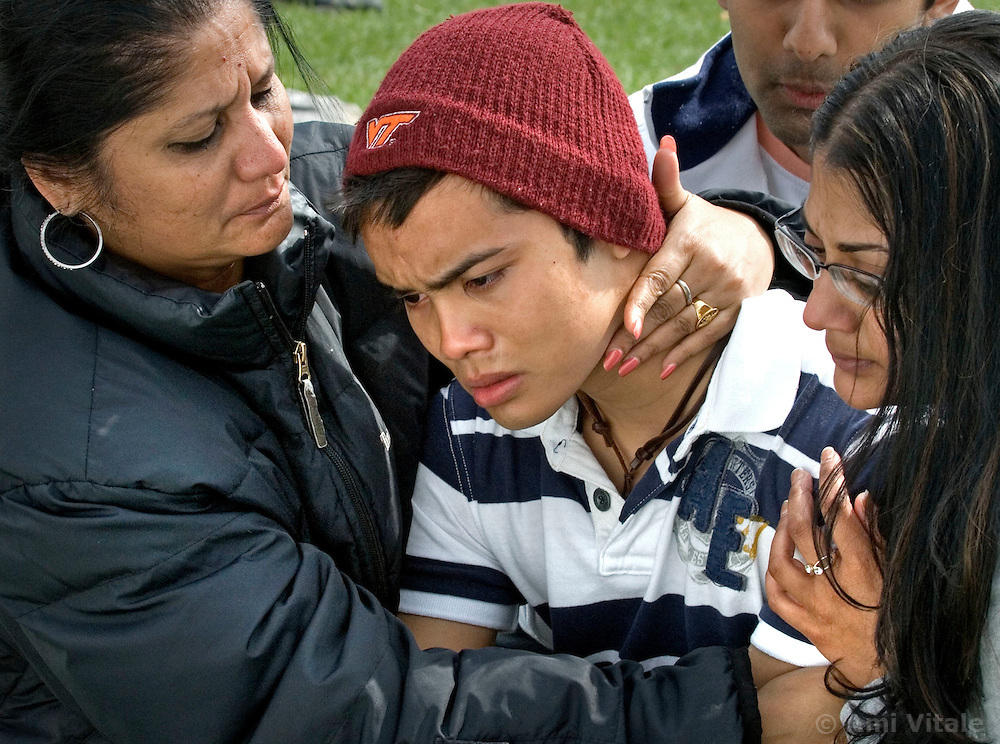 Blacksburg, Va. UNITED STATES: Ramon Cruz, a freshman at Virginia Tech, weeps at a memorial to the shooting victims at Virginia Tech in Blacksburg, Virginia April 18, 2007.  Gigi Giridhar, 51, the mother of his best friend Sanjay and Sanjay's sister Salvia comfort Cruz who lost a friend in the brutal slaying.  A 23-year-old student from South Korea was identified as the gunman who carried out the deadliest school shooting in US history.  33 people died on Monday, police named the gunman as Cho Seung-Hui, a student at the school and resident alien in the United States. (AMi Vitale)