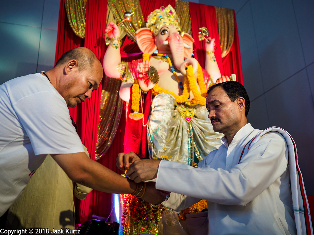 """23 SEPTEMBER 2018 - BANGKOK, THAILAND:  A Hindu priest gives a man a """"talika"""" at the Ganesha Festival at Wat Dan in Bangkok. Ganesha Chaturthi also known as Vinayaka Chaturthi, is the Hindu festival celebrated on the day of the re-birth of Lord Ganesha, the son of Shiva and Parvati. The festival, also known as Ganeshotsav (""""festival of Ganesha"""") is observed in the Hindu calendar month of Bhaadrapada, starting on the the fourth day of the waxing moon. The festival lasts for 10 days, ending on the fourteenth day of the waxing moon. Outside India, it is celebrated widely in Nepal and by Hindus in the United States, Canada, Mauritius, Singapore, Thailand, Cambodia, and Burma.   PHOTO BY JACK KURTZ"""