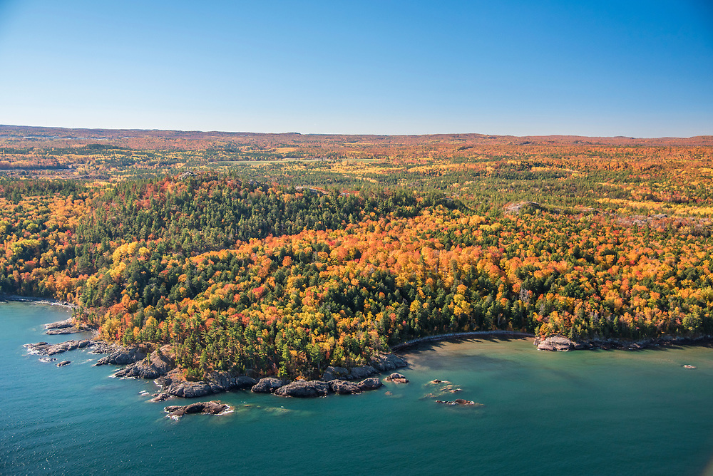 Aerial photography of the rugged Lake Superior shoreline north of Marquette, Michigan during fall color season. Areas shown include Wetmore Landing and Sugarloaf Mountain overlook.