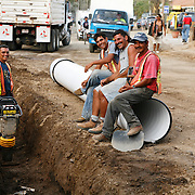 Municipal road workers and supervisor install part of a new storm drain system into Tamarindo's main road.