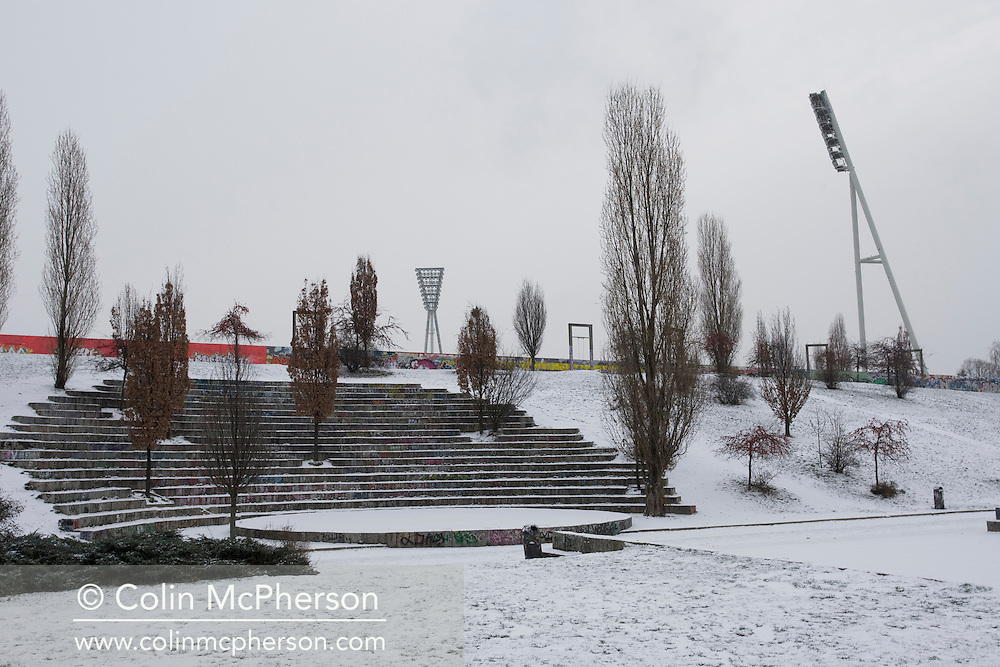 The Friedrich-Ludwig-Jahn Sportpark lying adjacent to a snow-covered section of the Mauerpark, a space dedicated to recreation along the route of the former Berlin Wall north of the city centre. The route of the Wall, which stood from 1962-1989, has been developed into the 'Mauerweg,' a thoroughfare which traces most of the route of the Wall which encircled the city and divided it into East and West Berlin during the Cold War. In the years following the 1989 civil uprising in the German Democratic.Republic, most of the Wall was removed as part of the reunification strategy which united the pro-Soviet DDR and the Federal Republic of (West) Germany.