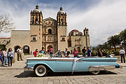 A classic Ford Galaxie Skyliner convertible car parked outside the Santo Domingo de Guzmán Church for a wedding in Oaxaca, Mexico.