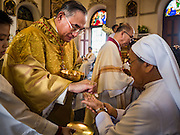 18 SEPTEMBER 2016 - BANGKOK, THAILAND:  FRANCIS XAVIER KRIENGSAK, the Archbishop of Bangkok, serves communion during the 100th anniversary mass at Santa Cruz Church. Santa Cruz Church was establised in 1769 to serve Portuguese soldiers in the employ of King Taksin, who reestablished the Siamese (Thai) empire after the Burmese sacked the ancient Siamese capital of Ayutthaya. The church was one of the first Catholic churches in Bangkok and is one of the most historic Catholic churches in Thailand. The first sanctuary was a simple wood and thatch structure and burned down in the 1800s. The church is in its third sanctuary and was designed in a Renaissance / Neo-Classical style. It was consecrated in September, 1916. The church, located on the Chao Phraya River, serves as a landmark for central Bangkok.      PHOTO BY JACK KURTZ