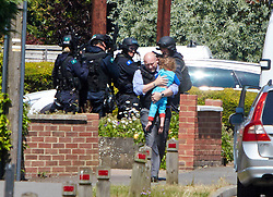 © Licensed to London News Pictures.  09/07/2013. OXFORD, UK.  Police officers carry a girl (dressed in blue) away from the scene of a standoff with a man thought to be armed with a shotgun. The man is believed to have taken his twin children hostage but both have now been released. Photo credit: Cliff Hide/LNP