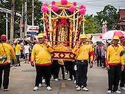 """23 JUNE 2015 - MAHACHAI, SAMUT SAKHON, THAILAND: Men carry the City Pillar Shrine through town during the procession for the shrine in Mahachai. The Chaopho Lak Mueang Procession (City Pillar Shrine Procession) is a religious festival that takes place in June in front of city hall in Mahachai. The """"Chaopho Lak Mueang"""" is  placed on a fishing boat and taken across the Tha Chin River from Talat Maha Chai to Tha Chalom in the area of Wat Suwannaram and then paraded through the community before returning to the temple in Mahachai.   PHOTO BY JACK KURTZ"""