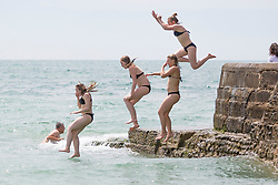 © Licensed to London News Pictures. 08/07/2017. Brighton, UK. A group of girls jumps of the pontoon in the sea as members of the public take advantage of the sunny weather to relax and sunbath on the beach in Brighton and Hove Photo credit: Hugo Michiels/LNP