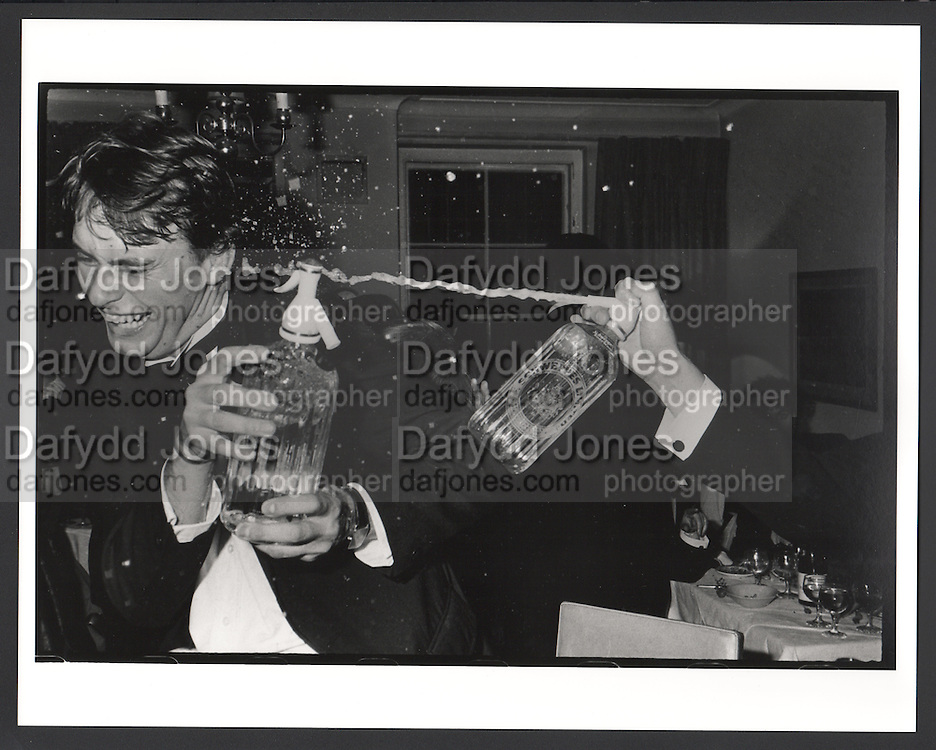 Clive Cooke at a party organised by Oliver Baxter. 149 Grosvenor St. London. 13 November 11981. Film. 81245f3. My way of photographing a party  has  been to try to show the interesting moments. I  knew these boys and I don't think they were acting up for me. I didn't look like a professional photographer and people didn't notice me much taking pictures. I would use a  small modest-looking Olympus rangefinder camera called an Olympus RC. The rangefinder allowed  focussing in low-light.  . It remains a little known classic.  Most of this evening  was actually boring. . Probably why someone picked up a soda siphon.  .