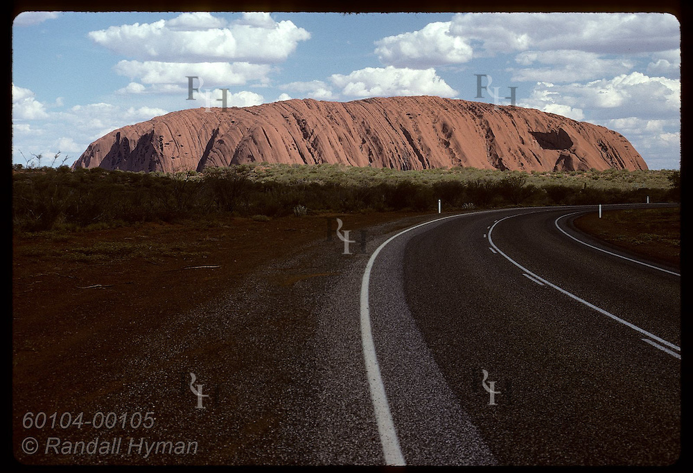 As highway curves off into distance, Ayers Rock looms on horizon; late afternoon, Uluru Natl Park Australia