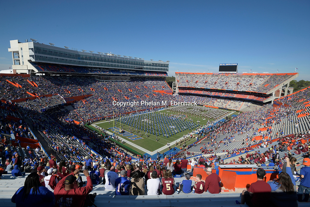 Fans watch as the marching bands from Florida, left, and Florida State perform before an NCAA college football game at Florida Field Saturday, Nov. 25, 2017, in Gainesville, Fla. (Photo by Phelan M. Ebenhack)