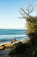 Homem visto de costas sentado sobre pedra na Praia da Daniela. Florianópolis, Santa Catarina, Brasil. / Rear view of a man sitting on a rock at Daniela Beach. Florianopolis, Santa Catarina, Brazil.