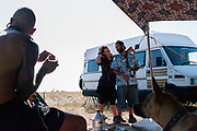 Dog looking at man with stretched ears and couple in front of white van, BulgariaTek, Bulgaria August 2011
