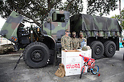 Three United States Marines pose for a photograph in front of a large military truck as they collect toys in their annual Toys for Tots Christmas initiative before the Miami Dolphins 2015 week 13 regular season NFL football game against the Baltimore Ravens on Sunday, Dec. 6, 2015 in Miami Gardens, Fla. (©Paul Anthony Spinelli)