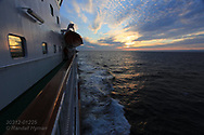 Hurtigruten cruise ship sails toward midnight sun in mid May along north coast near Belevag, Norway.