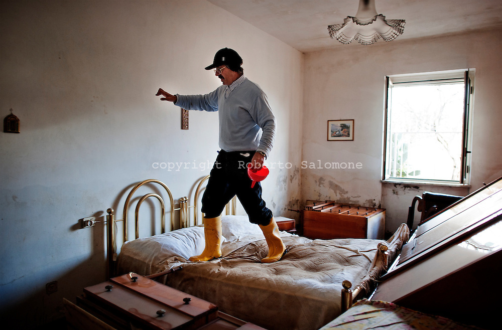 ITALY, Gromola : A man walks inside his damaged bedroom after a flooding hit his house on November 11, 2010. The flloding caused severe damages to the agricolture and buildings in the towns of gromola, Capaccio and Capaccio Scalo. AFP PHOTO / ROBERTO SALOMONE