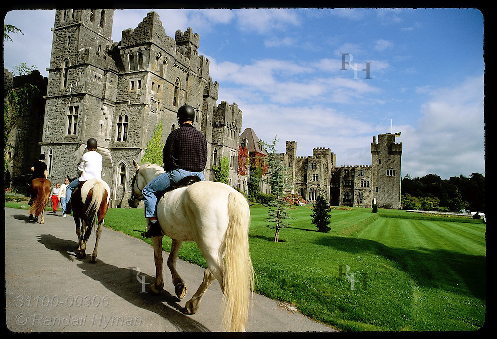 People ride horses along path outside Ashford Castle, an 83-room hotel counted among Ireland's finest; Cong, Ireland.