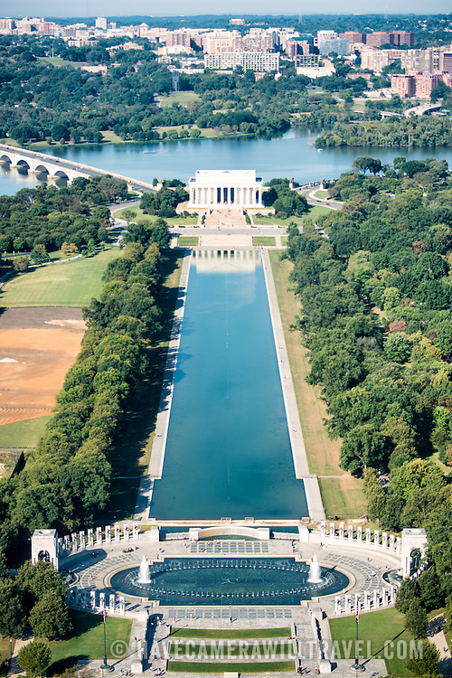 A view of National World War War Two Memorial (bottom), Reflecting Pool (middle) and Lincoln Memorial (top) from the top of the Washignton Monument. The Washington Monument stands at over 555 feet (169 metres) at the center of the National Mall in Washington DC. It was completed in 1884 and underwent extensive renovations in 2012-13 after an earthquake damaged some of the structure.