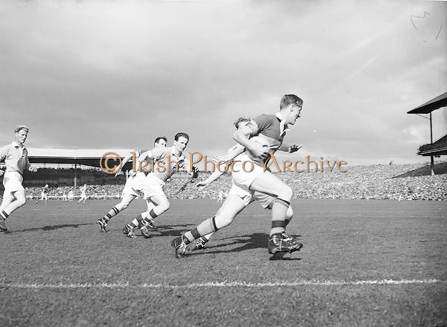 Kerry runs with the ball tucked under his arm as he is chased by Dublin during the All Ireland Senior Gaelic Football Final Kerry v Dublin in Croke Park on the 25th September 1955. Kerry 00-12 Dublin 01-06.