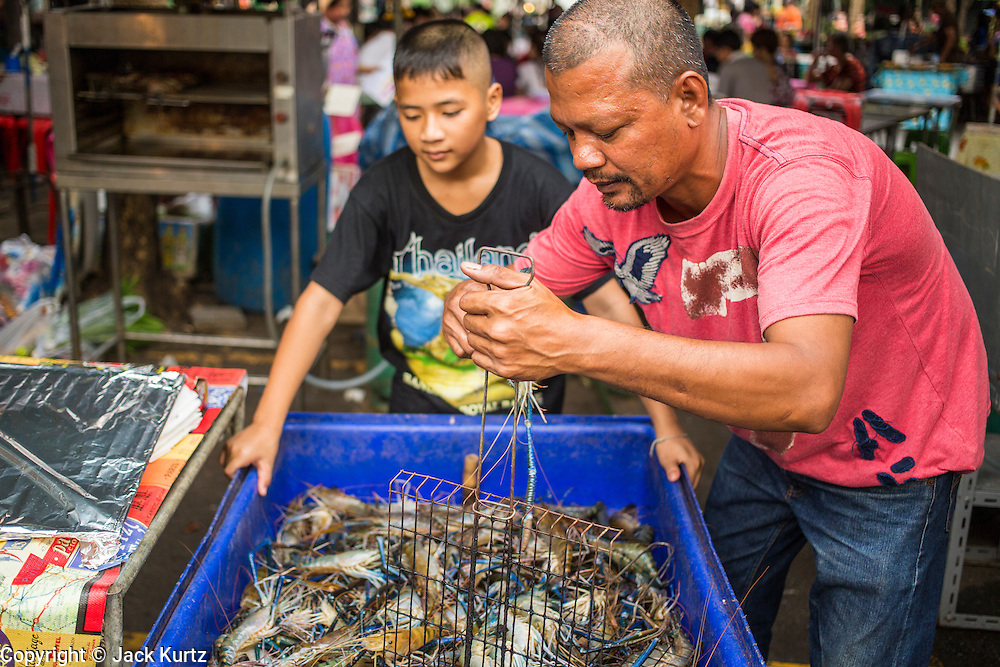 16 FEBRUARY 2013 - BANGKOK, THAILAND:     A restaurateur puts river prawn into a grill at Chatuchak Weekend Market in Bangkok. It is reportedly the largest market in Thailand and the world's largest weekend market. Frequently called J.J., it covers more than 35 acres and contains upwards of 5,000 stalls.      PHOTO BY JACK KURTZ