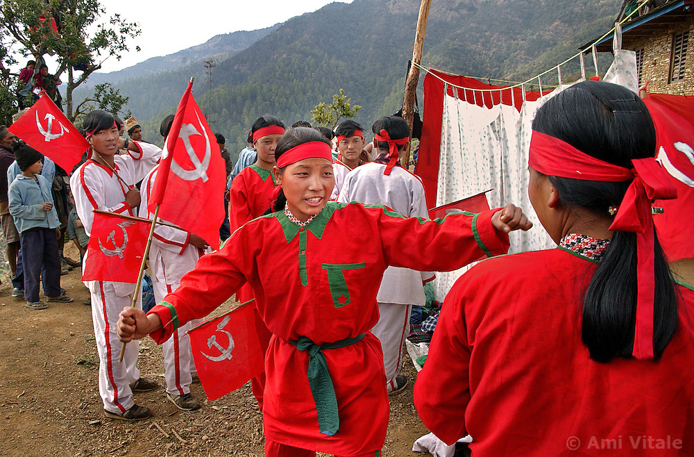 Maoists perform a traditional dance with Communist flags during  a cultural program where over 1000 villagers came from several kilometers walking distance in the village of Tila, district of Rolpa, Nepal March 14, 2005. The Maoists have these cultural programs several times every month as a way to educate villagers about their plans and programs. (Ami Vitale)