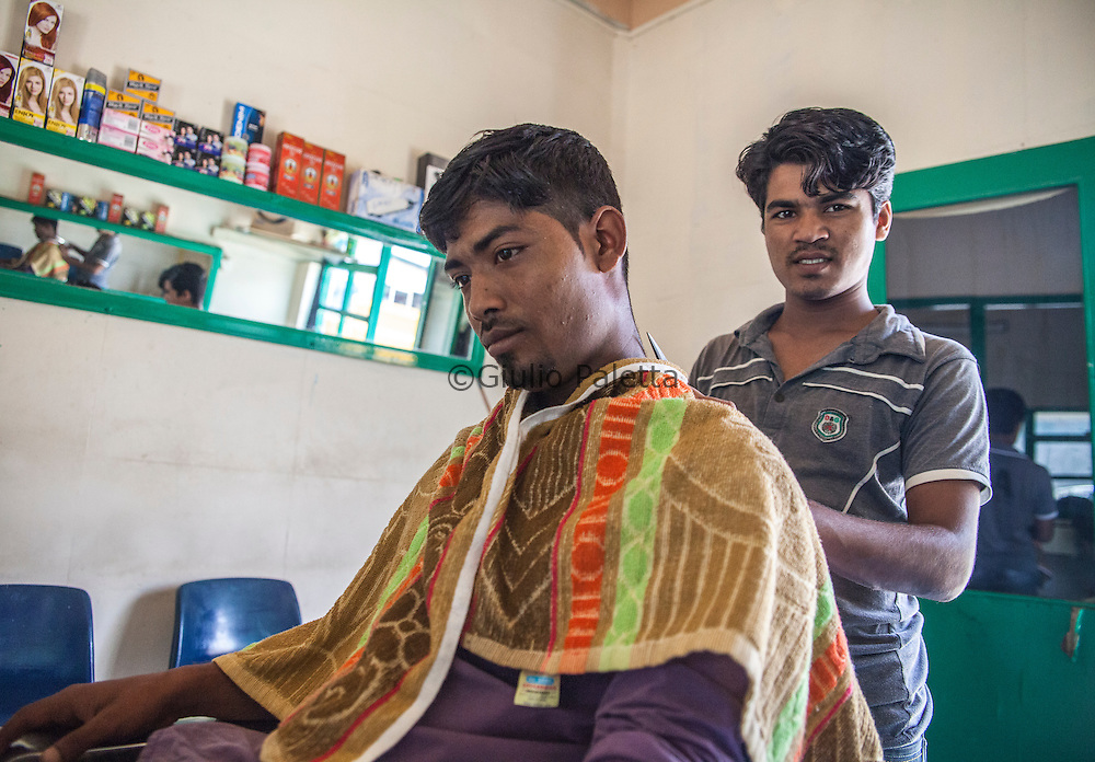 "Bengalese workers at a barber shop on Thilafushi island, the so-called ""rubbish island"". Created to collect and burn all the garbage coming from the capital island Male and all the tourists resorts"
