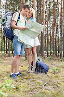 Full length of young hiking couple reading map in woods