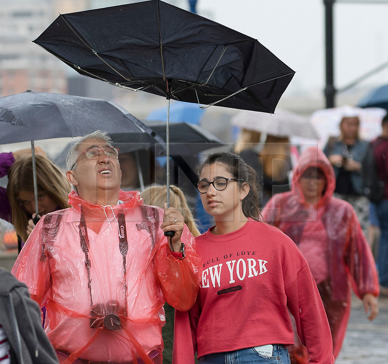 © Licensed to London News Pictures. 10/08/2018. London, UK.  Tourists are caught in a heavy rain shower and wet weather near the Tower of London at lunchtime today.  Photo credit: Vickie Flores/LNP