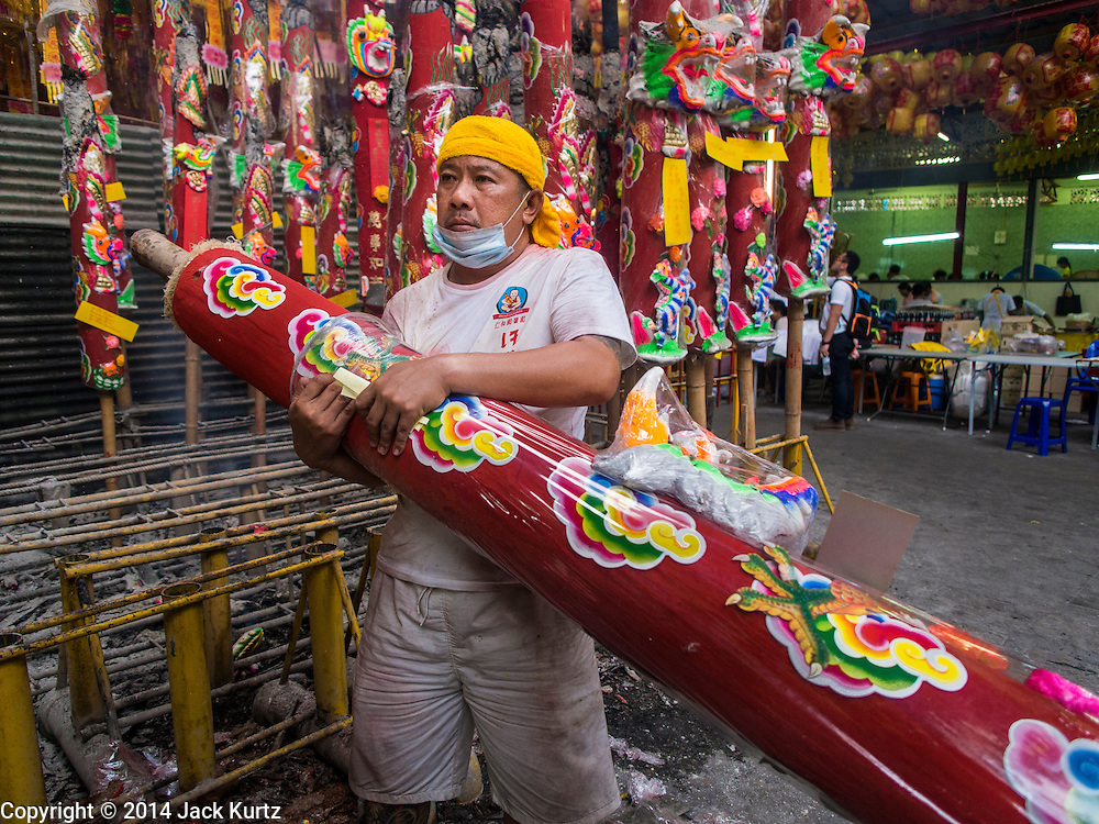 27 SEPTEMBER 2014 - BANGKOK, THAILAND: A temple attendant handles a  large prayer candle during the celebration of the Vegetarian Festival at the Chow Su Kong Shrine in Talat Noi, a Chinese enclave in Bangkok. The Vegetarian Festival is celebrated throughout Thailand. It is the Thai version of the The Nine Emperor Gods Festival, a nine-day Taoist celebration beginning on the eve of 9th lunar month of the Chinese calendar. During a period of nine days, those who are participating in the festival dress all in white and abstain from eating meat, poultry, seafood, and dairy products. Vendors and proprietors of restaurants indicate that vegetarian food is for sale by putting a yellow flag out with Thai characters for meatless written on it in red.   PHOTO BY JACK KURTZ