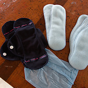 The contents of an Afripads kit, comprising pads, holders and a pouch. Started by volunteers in 2009, Afripads manufactures reusable fibre sanitary pads made locally by community residents. Beginning with a single employee, the company now employs roughly 100 women and produces approximately 700 kits (consisting of pads, holders and a bag) each week. At USh 12,000 to 15,0000 (£2.75 to £3.40) for a kit that lasts approximately one year, Afripads offer a significant saving over disposables which may cost in excess of USh 42,000 (£9.60) over the course of a year. And for the many girls and women who cannot afford disposables, they offer an affordable and more hygienic alternative to rags, cotton wool or toilet paper, all of which are frequently used. At schools where Afripads have been distributed, teachers report that absenteeism has dropped sharply as girls who previously did not have access to proper sanitary pads now no longer stay home when they have their periods.