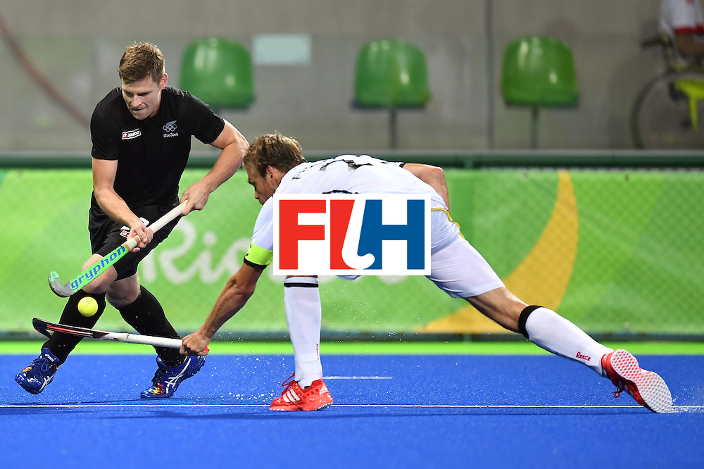 New Zealand's Stephen Jenness (L) vies with Germany's Moritz Furste during the men's quarterfinal field hockey Germany vs New Zealand match of the Rio 2016 Olympics Games at the Olympic Hockey Centre in Rio de Janeiro on August 14, 2016. / AFP / MANAN VATSYAYANA        (Photo credit should read MANAN VATSYAYANA/AFP/Getty Images)