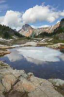 Partially thawed tarn, Yellow Aster Butte Basin. American Border Peak is in the distance. Mount Baker Wilderness, North Cascades Washington