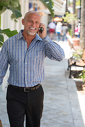 man enjoying talking on a cellphone while walking on the street in Fort Lauderdale, Florida