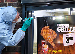 © Licensed to London News Pictures. 21/08/2018. London, UK. Forensics  examine a bullet hole in the window of Chicken Cottage on Rayners Lane, Harrow, north London, the scene of a double shooting. Armed police are reported to be searching the area after two men were shot in broad daylight. Their condition is unknown. This follows two separate shooting incidents in London yesterday. Photo credit: Ben Cawthra/LNP