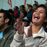 A young fan reacts to the action during the 'Titans of the Ring' wrestling group performance at El Alto's Multifunctional Centre. Bolivia. The wrestling group includes the fighting Cholitas, a group of Indigenous Female Lucha Libra wrestlers who fight the men as well as each other for just a few dollars appearance money. El Alto, Bolivia, 17th January 2010. Photo Tim Clayton