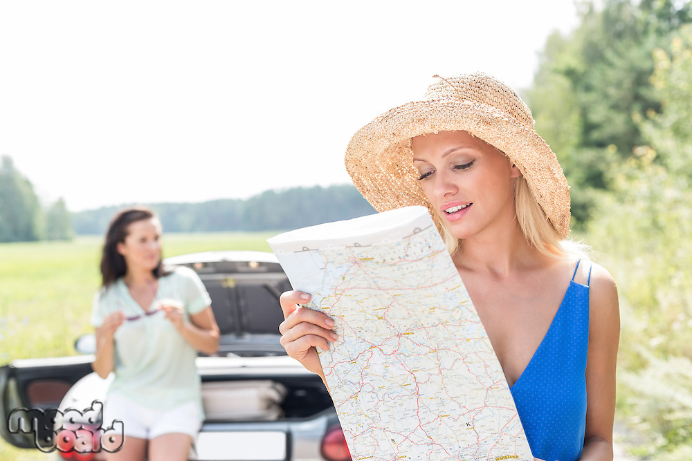Woman reading map while friend leaning on convertible in background