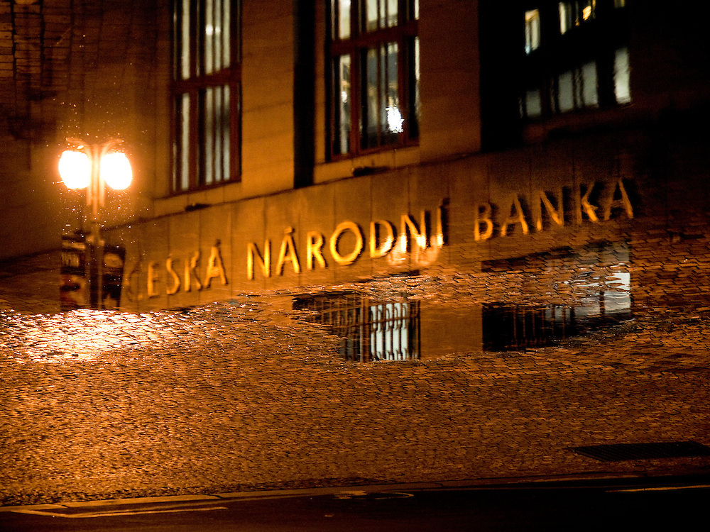"""Reflection of the Czech National Bank logo in a puddle at """"Na Prikope"""" street in the city center of Prague."""