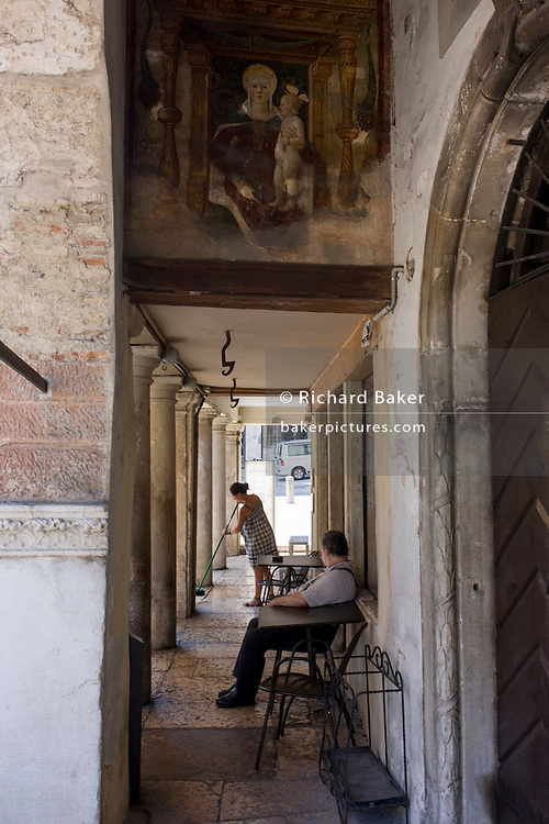 Beneath a religious frescoe, a woman sweeps the pavement while watched by local man in Vittorio Veneto, in the Province of Treviso, Veneto, Italy.