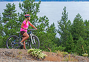 A woman mountain biking on Osprey Point in Ponderosa State Park above Payette Lake near the city of McCall in the Salmon River Mountains of central Idaho