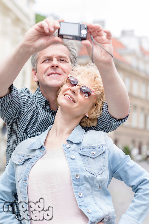 Happy middle-aged couple taking self portrait outdoors