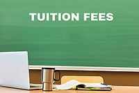 Tuition fee written on black board in classroom